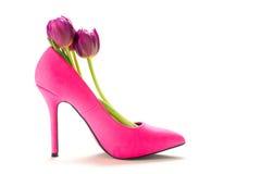 Rosa Schuh des hohen Absatzes der Damen mit Tulpen nach innen, lokalisiert auf Weiß stockfoto
