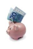 Schweinbank mit zwanzig Euros auf weißem Hintergrund Lizenzfreies Stockfoto