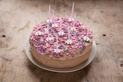 Rosa, selbst gemachter Geburtstagskuchen mit Herzsüßigkeiten und Blumenkerzen Stockfoto