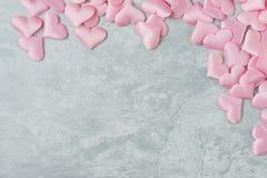 Rosa siden- hjärtor på grå ctone royaltyfria foton
