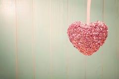 Rosa skinande hjärta på bakgrund för tappninggräsplanträ Arkivfoto
