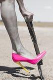 Rosa sko och skyffel för hög häl som gräver i sand Royaltyfria Foton