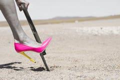 Rosa sko och skyffel för hög häl som gräver i smuts Royaltyfria Foton