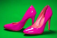 Rosa skor för höga häl på grön bakgrund Royaltyfri Bild