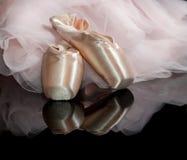 Rosa skor för satinebalettpointe på svart reflekterande bakgrund w Arkivfoton