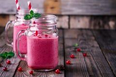 Rosa smoothie med lösa tranbär i murarekrus med mintkaramellen och sugrör på träbakgrund royaltyfri bild