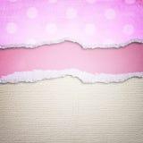 Rosa sönderrivet papper över texturerad kanfasbakgrund Arkivbilder