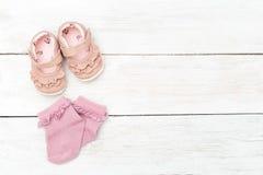 Rosa Socken und Schuhe für kleines Mädchen auf einem weißen hölzernen backgroun Lizenzfreies Stockfoto