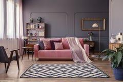 Rosa soffa med två filtar och kuddar som står i sammanträderoo Arkivbild