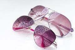 Rosa solglasögon och droppar på en bakgrund Arkivfoto
