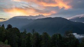 Rosa solnedgång över dalen som omges av berg och skogen royaltyfria bilder