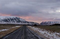 Rosa solnedgång över den isländska vägen Royaltyfri Foto