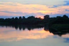 Rosa solnedgång över floden i sommar Arkivfoto