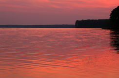 Rosa solnedgång över vatten Arkivfoton
