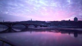 Rosa solnedgång ovanför den breda floden med bron på den härlig cityscape stock video