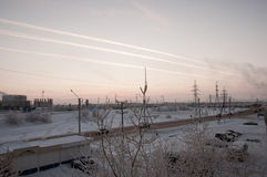 Rosa solnedgång på den industriella gatan för vinter med tryck i himlen efter flygplansikten från fönster i den kalla frostiga af Royaltyfri Foto