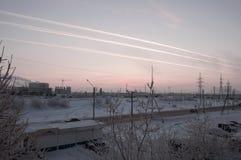 Rosa solnedgång på den industriella gatan för vinter med tryck i himlen efter flygplansikten från fönster i den kalla frostiga af Royaltyfri Bild