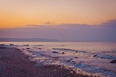 Rosa solnedgång på havet och ön i avståndet Arkivbild