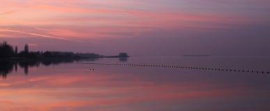 Rosa solnedgång på sjön Arkivfoto