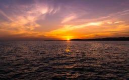 Rosa solnedgång på stranden med bergkonturn arkivbilder