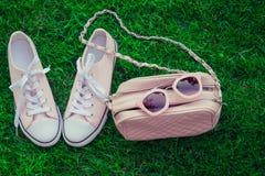Rosa Sonnenbrille auf einem rosa Geldbeutel und Turnschuhen Stockbild