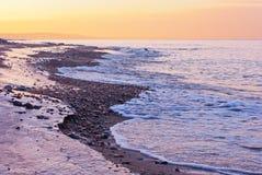 Rosa Sonnenuntergang auf dem Meer und der Insel im Abstand Stockfotografie