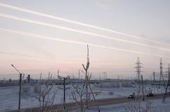 Rosa Sonnenuntergang auf der industriellen Straße des Winters mit Drucken im Himmel nach der Flugzeug Ansicht vom Fenster am kalt Stockfotos