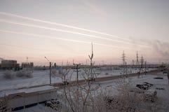 Rosa Sonnenuntergang auf der industriellen Straße des Winters mit Drucken im Himmel nach der Flugzeug Ansicht vom Fenster am kalt Lizenzfreies Stockfoto
