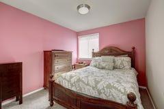 Rosa sovrum med sniden träsäng Arkivbilder