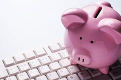 Rosa Sparschwein auf einer Computertastatur Stockfotos
