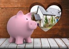rosa Sparschwein vor Holz mit Herzloch, in dem wir eine blaue Tür des Hauses sehen können (verwischt) Lizenzfreie Stockfotos