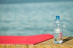 Rosa Sportmatte und Wasserflasche im Freien auf Seeufer Stockbild