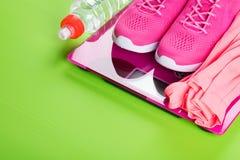 Rosa Sportturnschuhe und eine Weste auf den Skalen und eine Flasche Wasser, auf einem hellgrünen Hintergrund Stockfoto