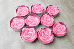 Rosa stearinljus är stora i mitten till dagen av St-valentin på en bakgrund av beige tyg Arkivfoton