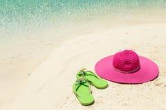 Rosa Strandhut und grüne Pantoffel im goldenen Sand durch Meer-shor Lizenzfreies Stockbild