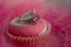 Rosa Strudel-kleiner Kuchen und ein Herz-Ring lizenzfreie stockbilder