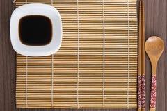 Rosa Sushiwerkzeuge und -bambus eine Matte Stockfotos