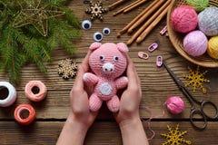 Rosa svin, symbol av 2019 lyckligt nytt år Virka leksaken för barn På tabellen dragar, visare, kroken, bomullsgarn Handgjorda han arkivbilder