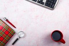 Rosa tabell för kontorsskrivbord med datoren, penna och en kopp kaffe, lott av saker Bästa sikt med kopieringsutrymme Arkivfoton