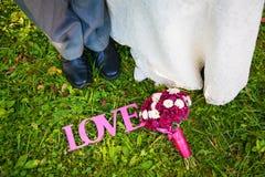 Rosa tecken av förälskelse och brud- bukett på gräset såväl som brud- och brudgumfoten Royaltyfri Bild