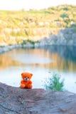 Rosa Teddybär über der Klippe in der untergehenden Sonne Stockbild
