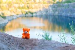 Rosa Teddybär über der Klippe in der untergehenden Sonne Lizenzfreies Stockbild