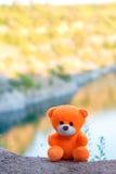 Rosa Teddybär über der Klippe in der untergehenden Sonne Lizenzfreies Stockfoto