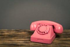 Rosa telefon för tappning på trätabellen med färgväggbakgrund fotografering för bildbyråer