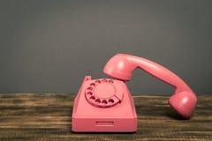 Rosa telefon för tappning på trätabellen med färgväggbakgrund arkivfoto