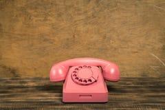 Rosa telefon f?r tappning p? tr?tabellen med f?rgv?ggbakgrund arkivfoton