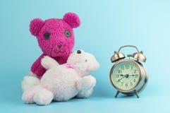 Rosa trägt Puppe und Wecker auf blauem Hintergrund, Konzept in der Liebe und Zeit Stockfotografie