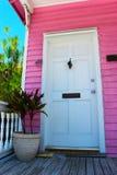 Rosa Tritonshorn-Haus mit weißer Tür Stockbild