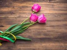 Rosa tulpan, blom- ordning på träbakgrund från gamla bräden och ett utrymme för meddelanden Bakgrund för moder` s Royaltyfri Foto