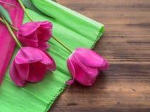 Rosa tulpan, blom- ordning på träbakgrund med dokument med olika förslag och utrymme för meddelande Bakgrund för dag för moder` s Arkivbild